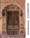 Painted and decorated wooden door entrance in Mehrangarh (Meherangarh) Fort, Jodhpur, Rajasthan, India. Ornate brass door set in white marble frame, stone carvings