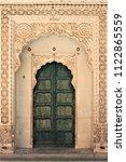 Wooden green door entrance in Mehrangarh (Meherangarh) Fort, Jodhpur, Rajasthan, India. Ornate brass door set in white marble frame.