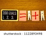 Small photo of Handwriting text 2018 Goals 1. 2. 3.. Concept meaning Resolution Organize Beginnings Future Plans White paper clip laid woody desk black slate some texts equal and plus mark.