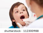 Say aaah - little boy having his throat examined by health professional - closeup - stock photo