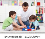 Father showing his sons a new toy - examining it together - stock photo