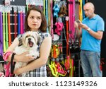 Stock photo sad upset young woman with dog in pet store during shopping with man 1123149326
