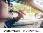 man driving car while eating... | Shutterstock . vector #1123204268