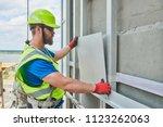 facade builder installing tile... | Shutterstock . vector #1123262063