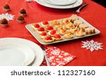 Decorated Christmas table with plate of tasty tartlets (cheese, tomatoes, seafood and foie gras) - stock photo