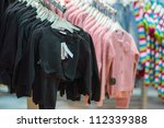 Sweaters on stands in kids mall - stock photo