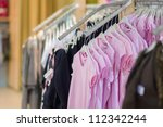 Variety of t-shirts and sweaters in kids mall - stock photo