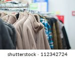 Variety of sweaters and vests on stands in supermarket - stock photo