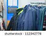 Variety of jackets, vests and sweaters on stands in supermarket - stock photo