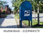 Small photo of Clarion, Pennsylvania / USA - June 29, 2018: USPS mailbox beside sidewalk