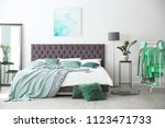 Stock photo stylish bedroom interior with clothes rack and mint decor elements 1123471733