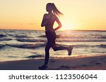 woman running alone at... | Shutterstock . vector #1123506044