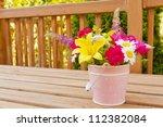 Flowers from the garden in pink bucket vase - stock photo