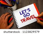 Small photo of Text sign showing Let'S Go Travel. Conceptual photo Going away Travelling Asking someone to go outside Trip Penholder notepad marker feelings ideas appointments information important.