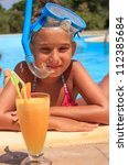 Girl drinking juice in the swimming pool - stock photo