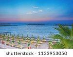 beach umbrellas and sunbeds on... | Shutterstock . vector #1123953050