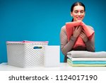 Small photo of Feel the fragrance. Smiling woman smelling clean softened linen. She is standing at white laundry board with closed eyes in content. Wicker clothesbasket is aside