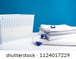 Small photo of Close up of wicker clothesbasket standing on table. Washing capsules are scattered on clean bath towels. Even the most stubborn stains will come off