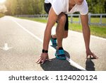 Small photo of Athletic man is using smartwatch while preparing for sprint on sunny road. He is staying in crouch start with hands touching asphalt. Male is having cardio exercises in open air concept
