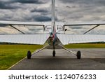 Symmetrical rear view of Cessna 172 Skyhawk 2 airplane on a runway with dramatic sky background.