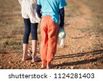 Small photo of poor little boy with toy in hand and girl barefooted refugees standing in hot desert