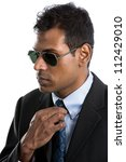 Indian business man wearing a suit and sunglasses. Isolated against a white background - stock photo
