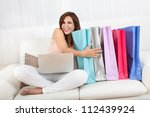 woman sitting on sofa holding... | Shutterstock . vector #112439924