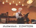 an elderly shoemaker with a... | Shutterstock . vector #1124470286