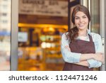 smiling young owner in uniform... | Shutterstock . vector #1124471246