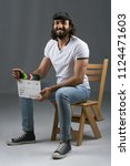 Small photo of Side shot of a director wearing a casual outfit, sitting on a wooden chair, holding capper board and smiling