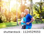 happy senior couple jogging... | Shutterstock . vector #1124529053