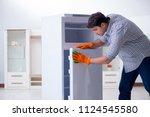 man cleaning fridge in hygiene...   Shutterstock . vector #1124545580