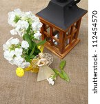 Composition from the bouquet of phloxes, lantern and straw angel on a canvas table - stock photo