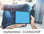 man using tablet pc while lying ... | Shutterstock . vector #1124621429