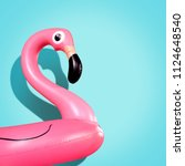 Small photo of Giant inflatable Flamingo on a blue background, pool float party, trendy summer concept