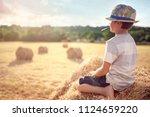 boy sitting on a haystack... | Shutterstock . vector #1124659220