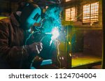 the worker in overalls and a... | Shutterstock . vector #1124704004