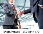 two businessmen shaking hands... | Shutterstock . vector #1124844479