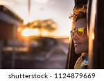 beautiful woman travel on a car looking outside and enjoy the light of the golden sunset on her face. nice lifestyle and peaceful emotions traveling around the world