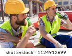 two young workers smiling ... | Shutterstock . vector #1124912699