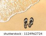 flip flops on a sandy ocean...   Shutterstock . vector #1124962724