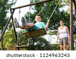 mother swinging her son on a... | Shutterstock . vector #1124963243