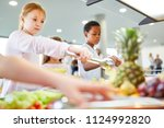 Stock photo students in elementary school take fruit at the buffet in the cafeteria 1124992820