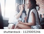 Small photo of Two beautiful african girl in sleepwear smiling sitting on bed at home woke up in the morning on a sunny day. Women share make-up and tidy themselves up