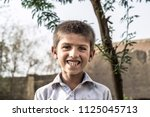 Stock photo a poor homeless happy smiling orphan child 1125045713