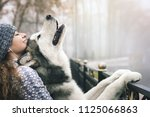 Stock photo image of young girl with her pet cute dog alaskan malamute outdoor at autumn or winter domestic 1125066863
