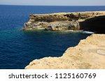 Rocky coastline with clear blue water in the ocean in Gozo, Malta in Europe