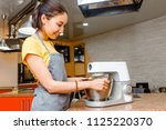 woman cooking in apron using... | Shutterstock . vector #1125220370