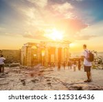 people walking around the ruins ... | Shutterstock . vector #1125316436