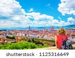 Stock photo woman tourist in red admires florence firenze duomo arno river towers cathedrals tiled roofs 1125316649